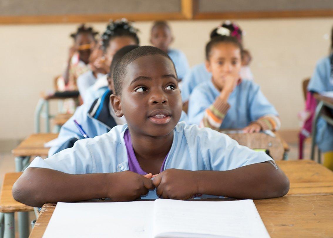 Un enfant africain est assis à son bureau, dans une école d'un village d'enfants SOS.