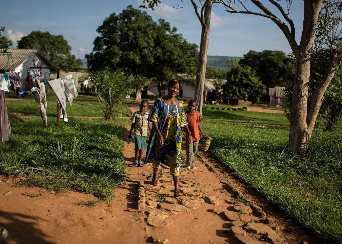 Accompagnée de ses enfants, une mère traverse un village d'enfants SOS en Afrique.