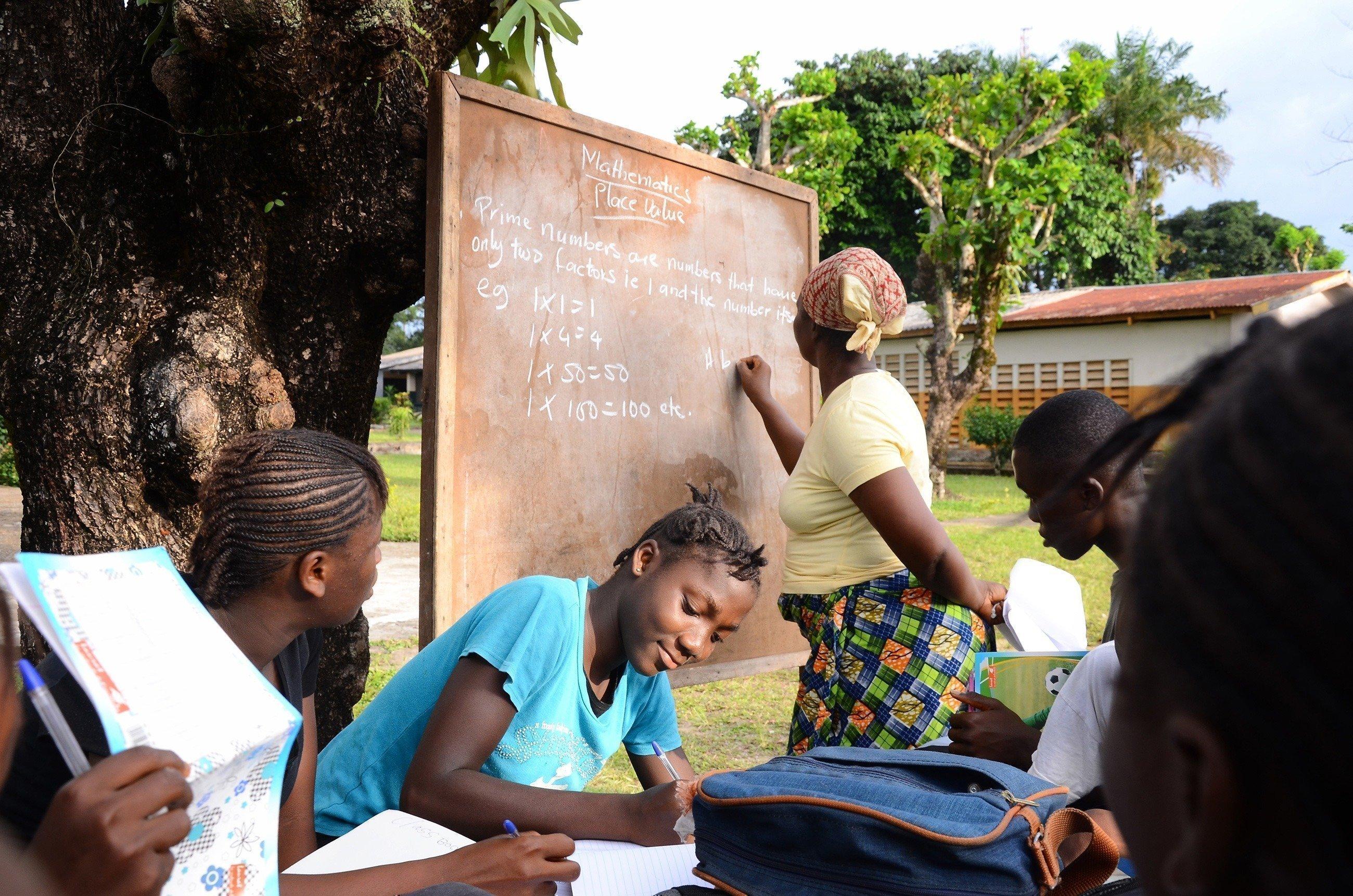 Des enfants apprennent la leçon sur une ardoise.