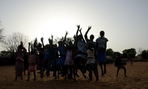 Les élèves d'une classe africaine d'un village d'enfants SOS sautent en l'air de joie.