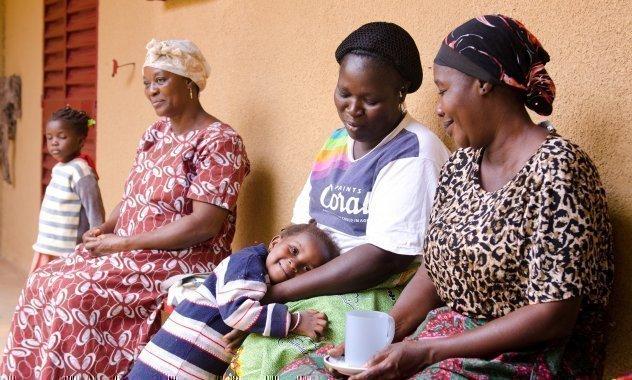 Trois mères africaines d'un village d'enfants assises sur un banc devant une maison. Une mère prend son enfant dans ses bras.