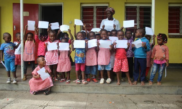 Les écoliers africains d'un village d'enfants SOS brandissent leurs bulletins scolaires.