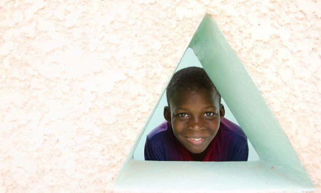 Un garçon regarde par une fenêtre triangulaire.