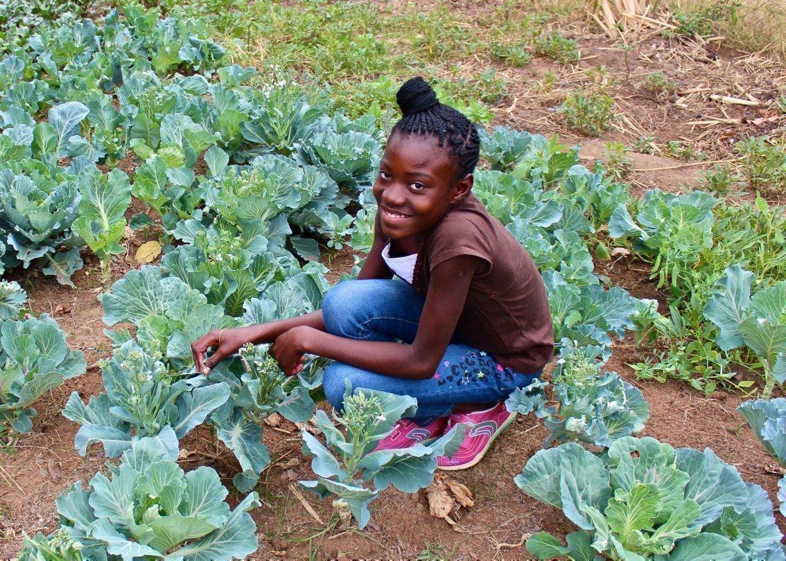Afrikanisches Kind aus einem SOS-Kinderdorf sitzt im Gemüsebeet und kümmert sich um den Salat.