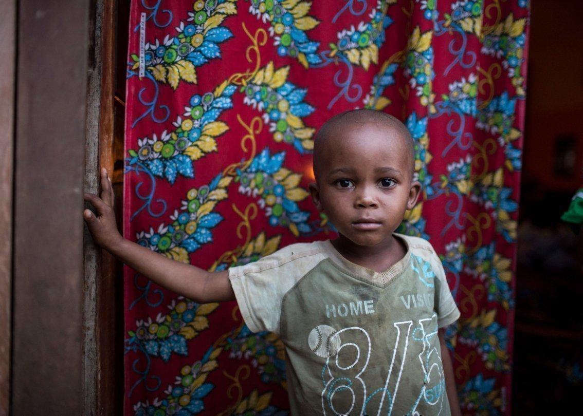 Un petit garçon se teint devant un tapis multicolore et regarde vers l'appareil photo.