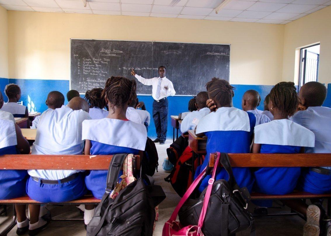 Plusieurs enfants en uniforme, assis sur des bancs d'école, écoutent leur professeur.