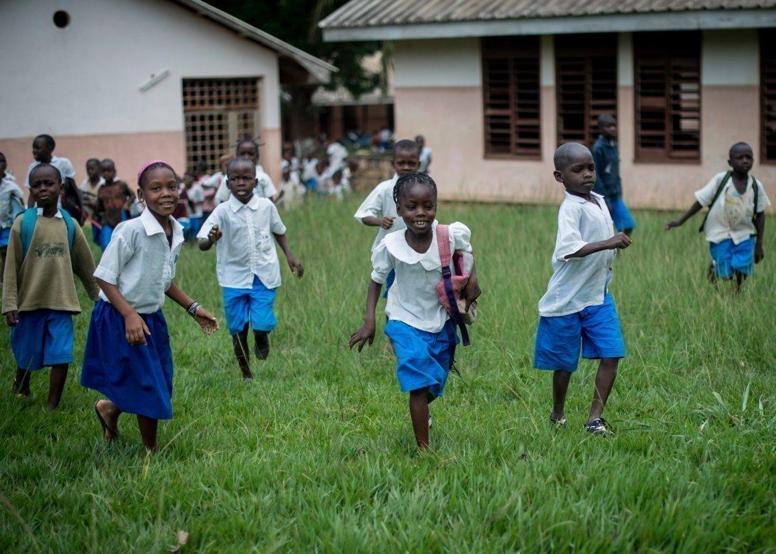 Des enfants sortent de l'école en courant, après leur journée de cours.
