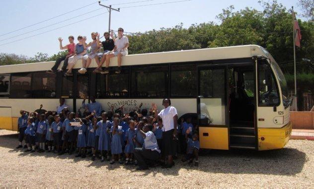 Une classe devant un autocar, sur lequel des collaborateurs SOS sont assis.
