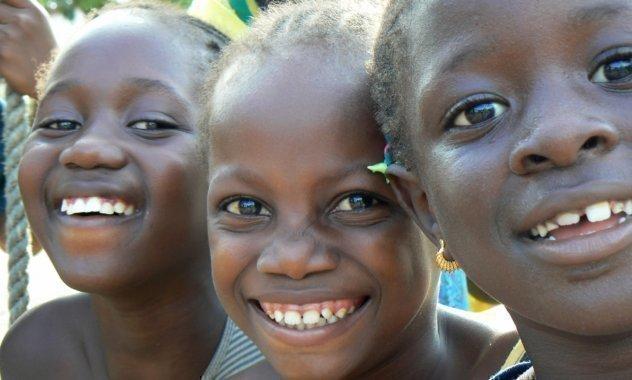 Trois petites filles sourient.