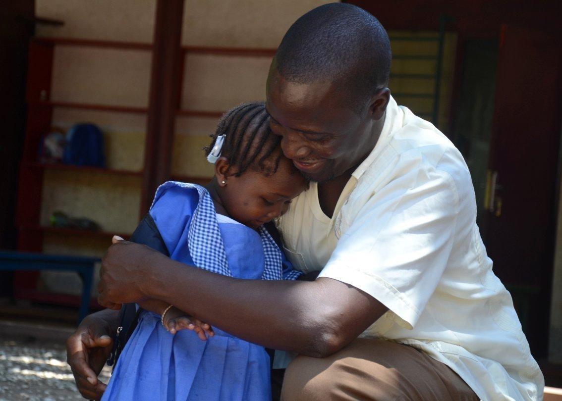 Un papa SOS prend une petite fille dans ses bras.