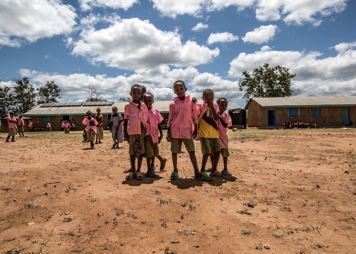 Des écoliers vêtus d'une chemise rose devant leur école.