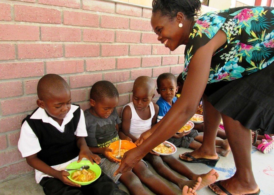 Une maman SOS nourrit des enfants.
