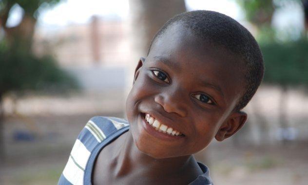 Un garçon à l'air joyeux fait un sourire à l'appareil photo.