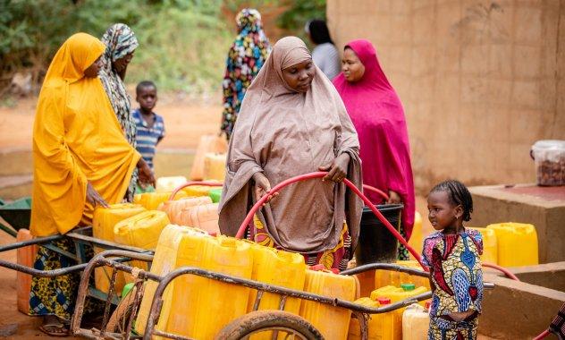 """Eine der Frauengruppen des Komitees """"Borne Fontaine"""" schöpfen Wasser am Brunnen."""